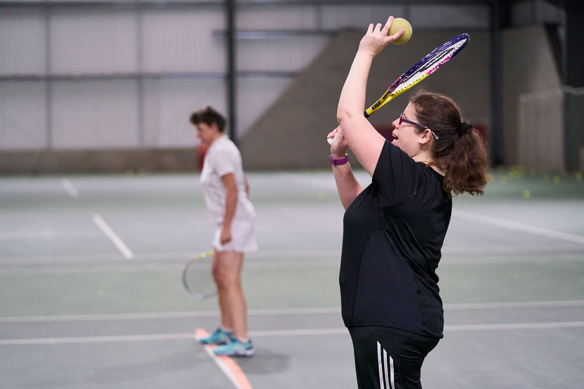 visually impaired woman preparing to hit tennis serve