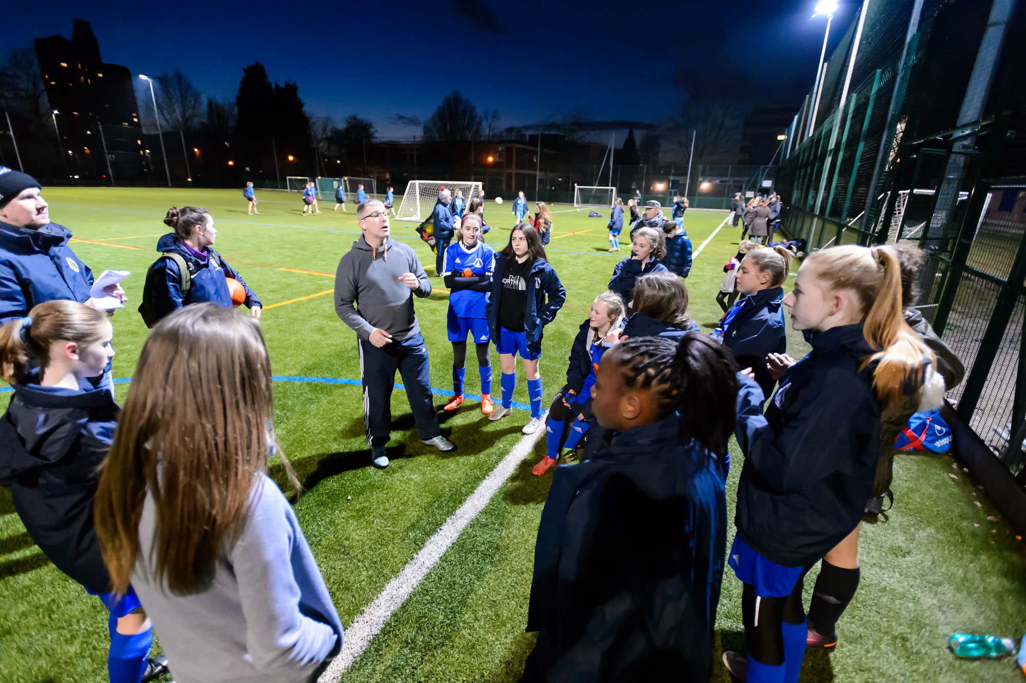 A coach speaks to players ahead of a girls' football session