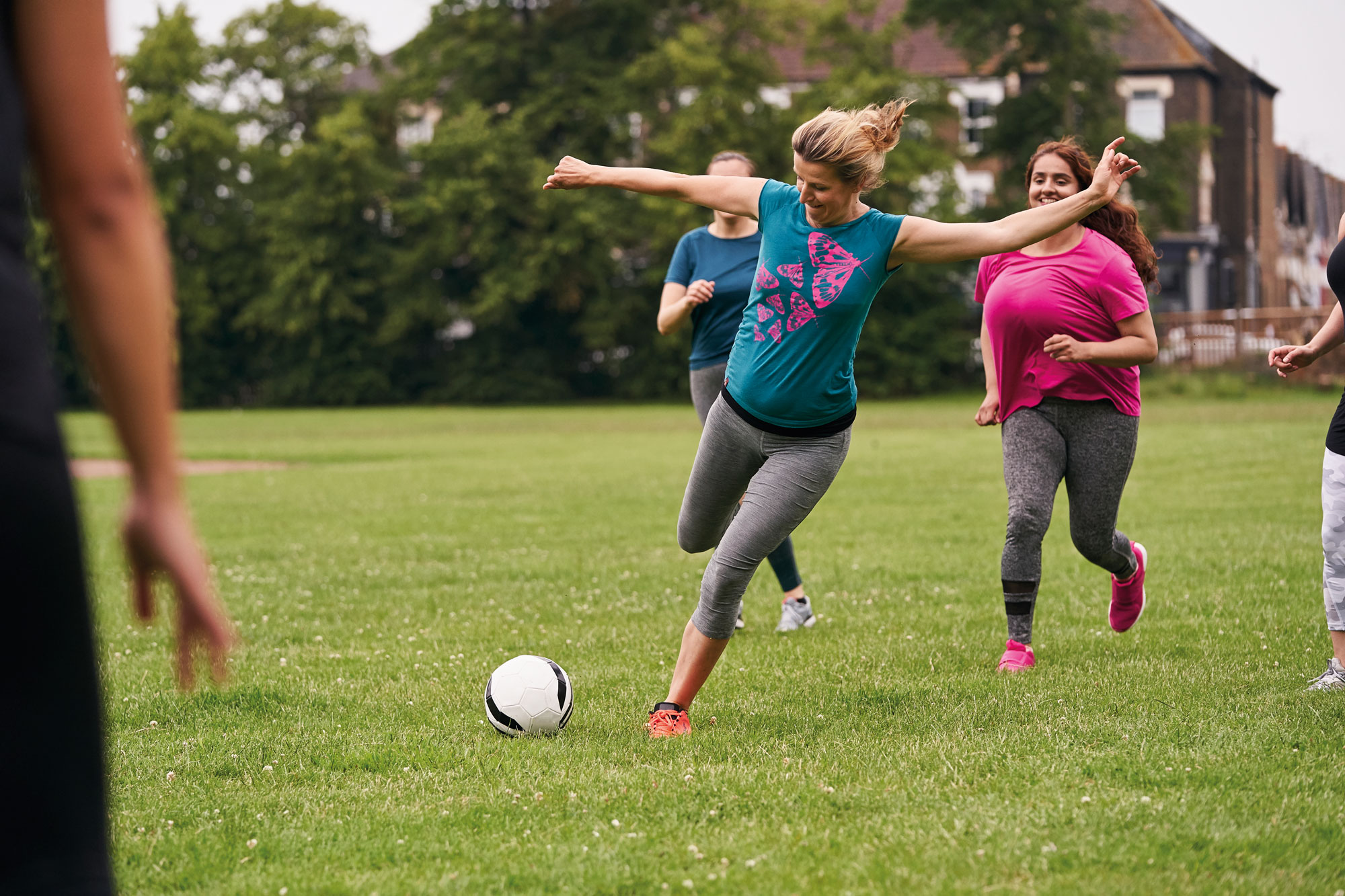 Woman kicking football