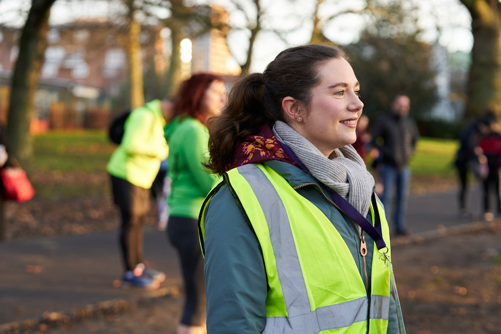 Woman in high vis jacket stewarding community run